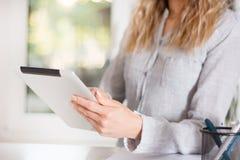 拿着数字式片剂的典雅的女商人在现代办公室和工作 免版税库存照片