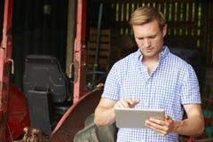 拿着数字式片剂的农夫站立在有老Fashione的谷仓 免版税库存图片