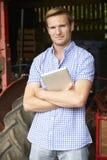拿着数字式片剂的农夫站立在有老Fashione的谷仓 库存照片