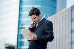 拿着数字式片剂的商人站立户外工作户外商业区 免版税库存照片