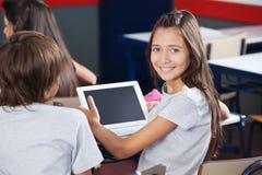 拿着数字式片剂的女小学生在书桌 库存图片