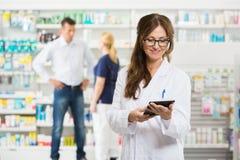 拿着数字式片剂的女性药剂师在 免版税库存照片