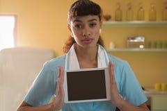 拿着数字式片剂的女服务员在餐馆 免版税库存照片