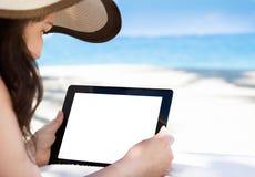 拿着数字式片剂的妇女在海滩 库存照片