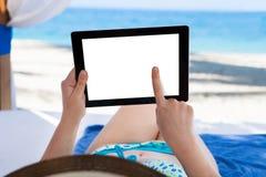 拿着数字式片剂的妇女在海滩 图库摄影