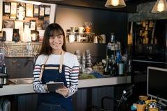 拿着数字式片剂的微笑的亚洲barista画象在coun 免版税库存图片