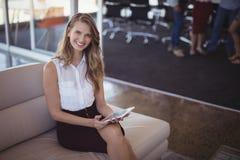 拿着数字式片剂的微笑的女实业家画象,当坐沙发时 免版税库存图片