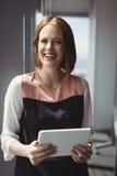拿着数字式片剂的微笑的执行委员画象 图库摄影