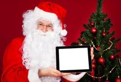 拿着数字式片剂的愉快的圣诞老人的画象 免版税图库摄影