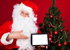 拿着数字式片剂的愉快的圣诞老人的画象 图库摄影