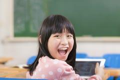 拿着数字式片剂的愉快的矮小的女小学生 库存照片