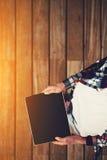 拿着数字式片剂的格子花呢上衣和白色T恤杉的女孩 免版税库存照片