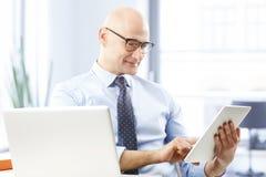 拿着数字式片剂的生意人 免版税库存图片