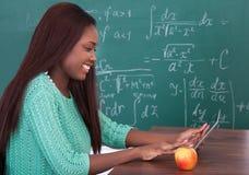 拿着数字式片剂的老师在学校书桌 免版税库存图片