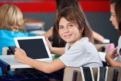 拿着数字式片剂的逗人喜爱的男小学生在教室 免版税库存图片