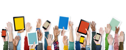 拿着数字式设备的不同的手 免版税库存图片