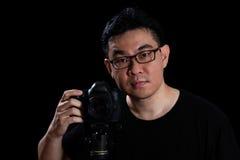 拿着数字式SLR照相机的亚裔中国男性摄影师 免版税库存照片