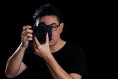 拿着数字式SLR照相机的亚裔中国男性摄影师 库存照片