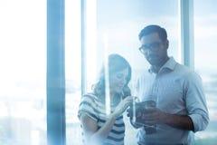 拿着数字照相机的企业夫妇反对玻璃窗在办公室 库存照片