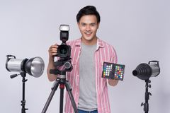 拿着数字照相机的年轻亚裔摄影师,当工作i时 图库摄影
