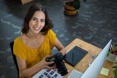 拿着数字照相机的微笑的图表设计师在创造性的办公室 免版税库存照片