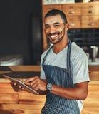拿着数字片剂的一男性barista在咖啡馆的柜台 库存照片