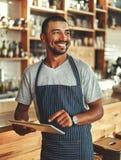 拿着数字片剂的年轻男性所有者,当站立在咖啡馆时 库存图片