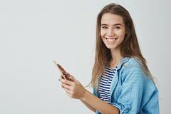 拿着数字片剂的迷人的愉快的微笑的女孩享用使用全新的咧嘴小配件转动的照相机快乐 免版税库存图片