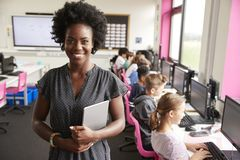 拿着数字片剂高中生的教学线女老师画象坐由在计算机类的屏幕 库存照片