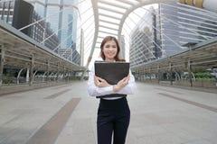 拿着文件文件夹的可爱的年轻亚裔女商人画象在都市城市背景边路  免版税图库摄影