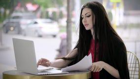拿着文件的年轻女人看在证券交易所的膝上型计算机新闻 股票录像
