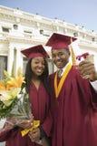 拿着文凭和花的两个毕业生 库存照片