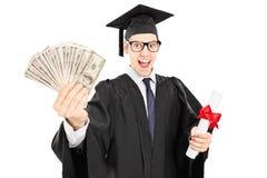 拿着文凭和金钱的年轻大学毕业生 免版税库存图片