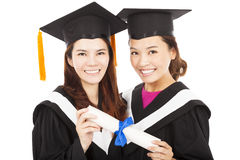 拿着文凭的两名微笑的年轻毕业生学生 免版税库存图片