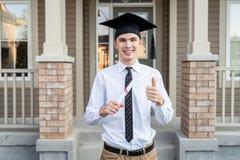 拿着文凭的年轻男生,当戴着在房子前面时的毕业帽子,当举行赞许时 免版税库存照片