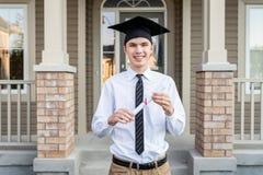 拿着文凭的年轻男生,当戴着在房子前面时的毕业帽子 库存照片