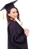 拿着文凭的毕业褂子的美丽的女学生 免版税库存图片