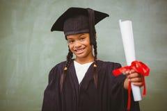 拿着文凭的毕业长袍的小女孩 免版税库存照片