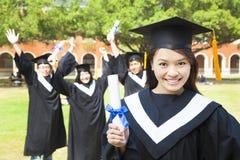 拿着文凭的美丽的女性大学毕业生在仪式 免版税库存照片