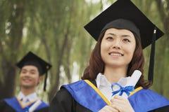 拿着文凭,前面的妇女的两个年轻人大学毕业生 免版税库存照片