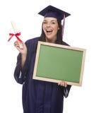 拿着文凭,空白的Chalkboar的方帽与长袍的女性毕业生 图库摄影