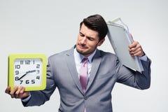 拿着文件夹和时钟的失望的商人 库存照片