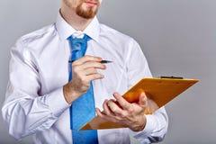 拿着文件夹和笔的商人 库存照片