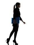 拿着文件夹文件走的剪影的女商人 免版税库存图片