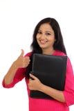 拿着文件夹的愉快的女学生 图库摄影