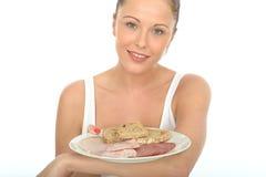 拿着斯堪的纳维亚早餐的健康愉快的年轻woma n 免版税库存图片
