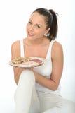 拿着斯堪的纳维亚样式冷盘的健康愉快的年轻woma n 图库摄影