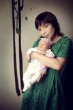 拿着新出生的女婴的年轻亚裔母亲 免版税库存照片