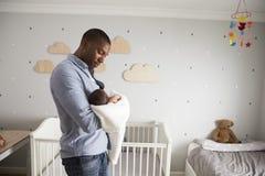 拿着新出生的小儿子的父亲在托儿所 免版税库存照片