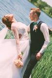 拿着新娘的新郎在池塘附近 免版税图库摄影